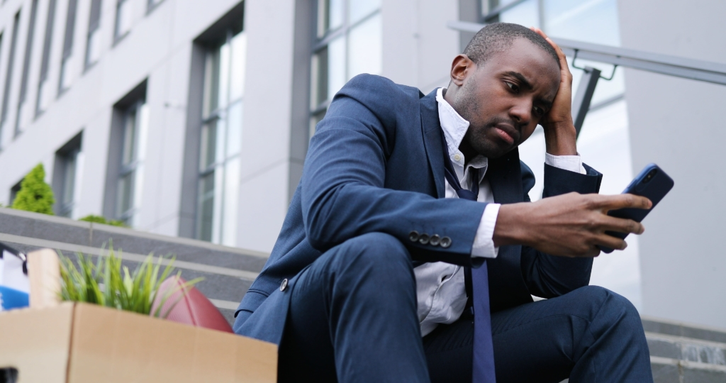 A man sits next to a box of his belongings while he uses his phone to look up how to apply for UIF. Little does he know this process could be made easier with an lawyer and affordable legal insurance.
